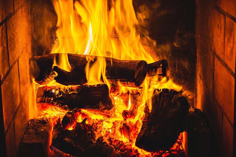 Close-up of bonfire on wooden log at night