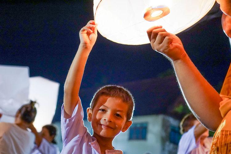Portrait of boy holding illuminated lantern during event