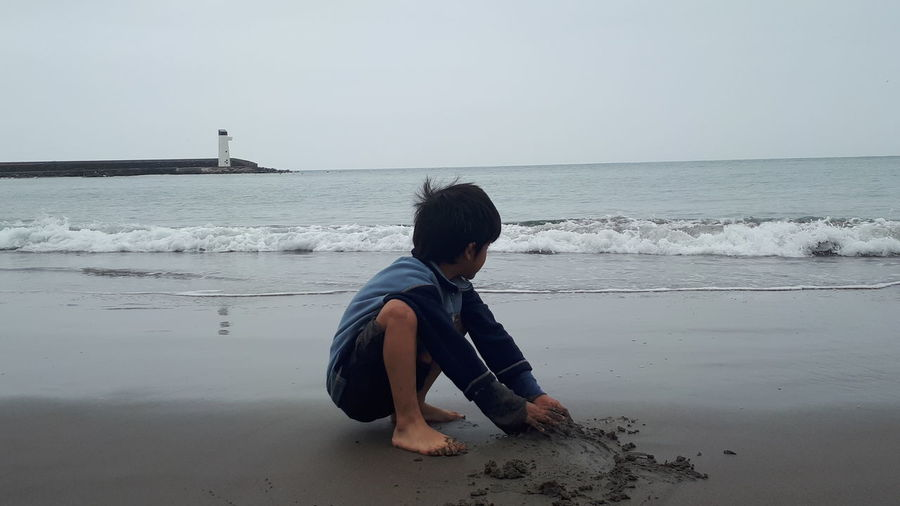 Boy playing with sand at beach