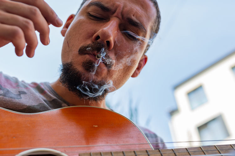Low angle view of man smoking while playing guitar outdoors