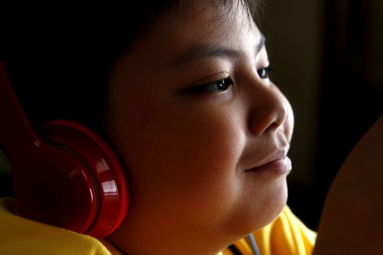Close-Up Of Boy Listening To Headphones