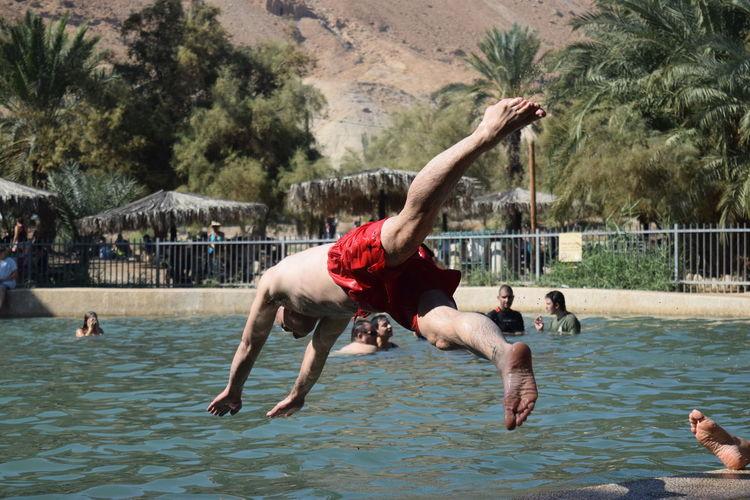Shirtless man diving into swimming pool at tourist resort