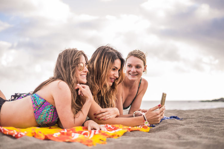 Smiling friends using mobile phone while lying on sand at beach