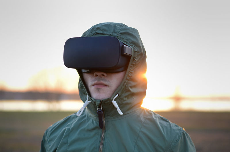 Man wearing virtual reality simulator standing on beach