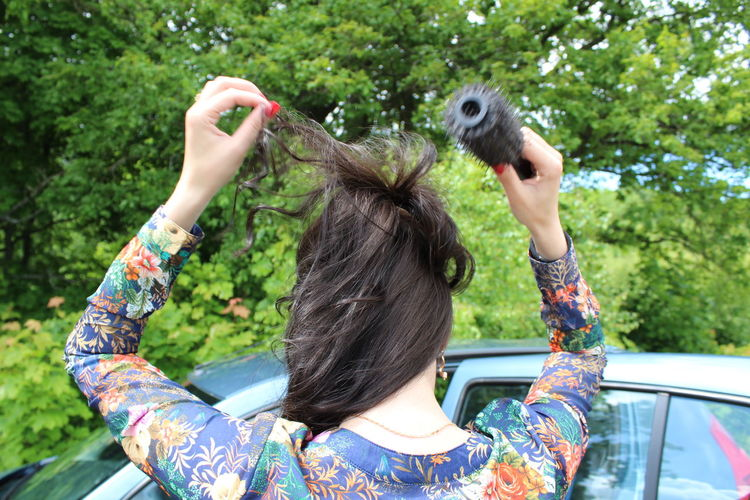 Rear view of woman combing hair by car against trees