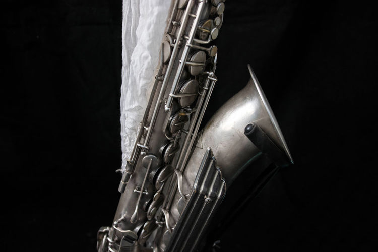 A silver saxophone decorated with a white cloth. Artistic Brass Instrument  Music Sax Shiny Arts Culture And Entertainment Black Background Brass Close-up Cloth Decoration Metal Metallic Music Musical Equipment Musical Instrument No People Saxophone Silver Colored Studio Shot White Wind Instrument