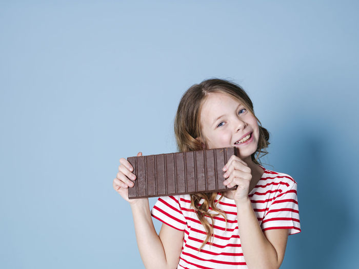 Girl Child Chocolate Bar BIG Huge Brown Sweet Hold Food Candy Nutrition Unhealthy Teeth Calories Nerves Happy Cocoa Reward Laugh Joy Posen Model Copy Space Concept Energy Sugar Ration Sweet Tooth Nibble Chomp Munch Delicious Good Addictive Intoxication Beautiful Smiling Happiness Portrait One Person Childhood Girls Front View Looking At Camera Striped Holding Women Casual Clothing Indoors  Offspring Emotion Females Innocence Hair Hairstyle Blue Background Pre-adolescent Child