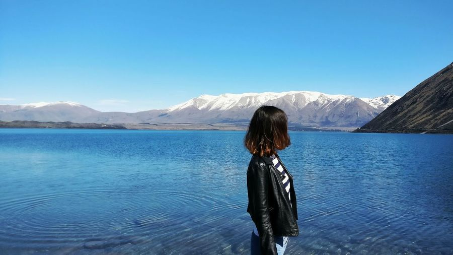 Side View Of Woman Standing By Lake Against Mountains And Clear Blue Sky