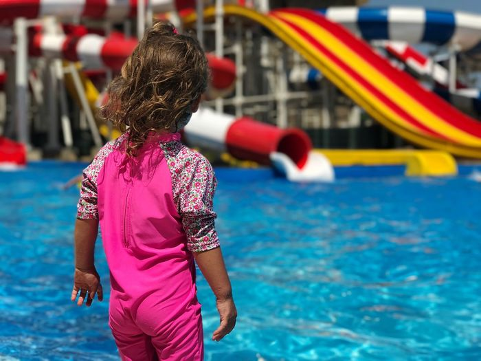 Rear view of girl standing at water park