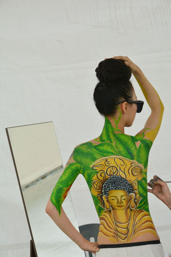 Rear view of shirtless woman with painted back standing against wall