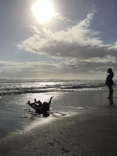 Girl playing in the surf Cocoa Beach, Florida Dawn Light Silhouettes Silhoutte Photography Beach Silhouettes Shimmering Shimmering Waters Beach Horizon Over Water Mom And Daughter Girl On The Shore Pregnant Woman
