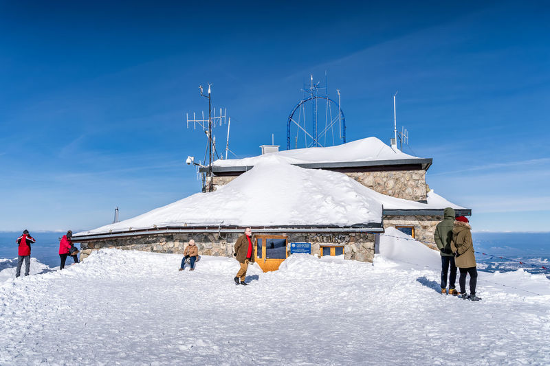 People on snow covered mountain against blue sky