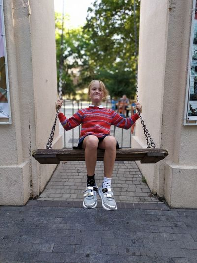 Full length portrait of smiling girl sitting on swing outdoors