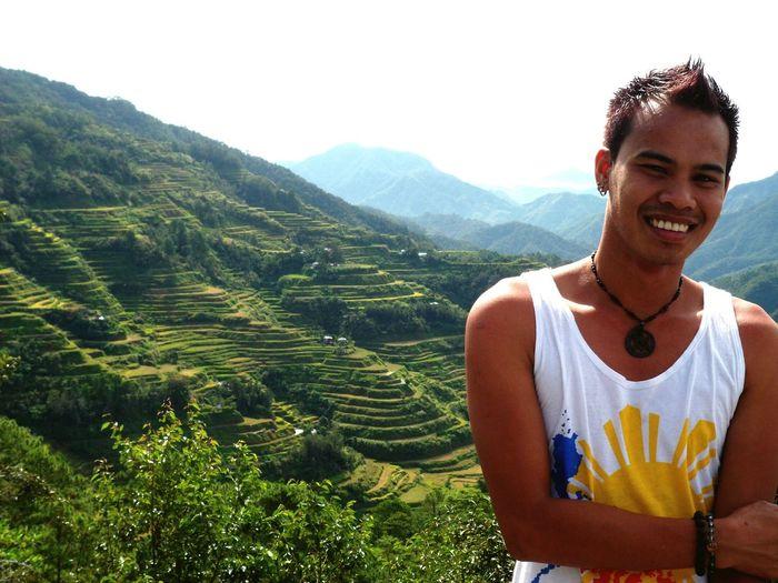 Portrait Of Happy Man Standing Against Banaue Rice Terraces