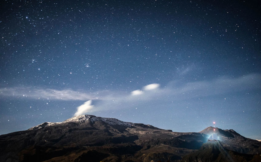 Scenic view of majestic mountains against sky at night