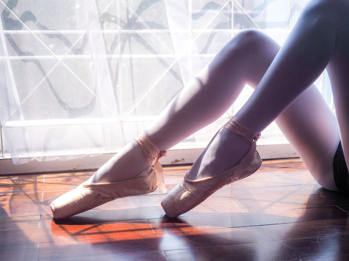 Low section of ballet dancer on window sill
