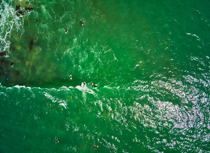 Surfers on Water Water Green Color Sea Nature Day High Angle View Beauty In Nature Outdoors Swimming Motion Sport Waterfront Power In Nature Turquoise Colored Surfers Droneshot Drone  View From Above Surfers In The Water View From Above