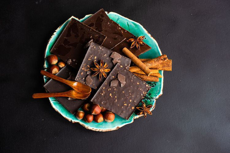 High angle view of chocolate bars with spices and nuts in plate on table