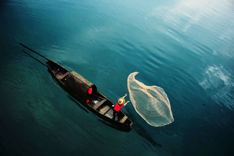 High Angle View Of Man On Boat Throwing Fishing Net