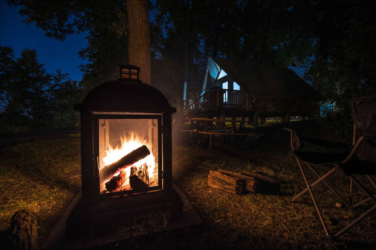 View of bonfire on wooden structure against trees at night