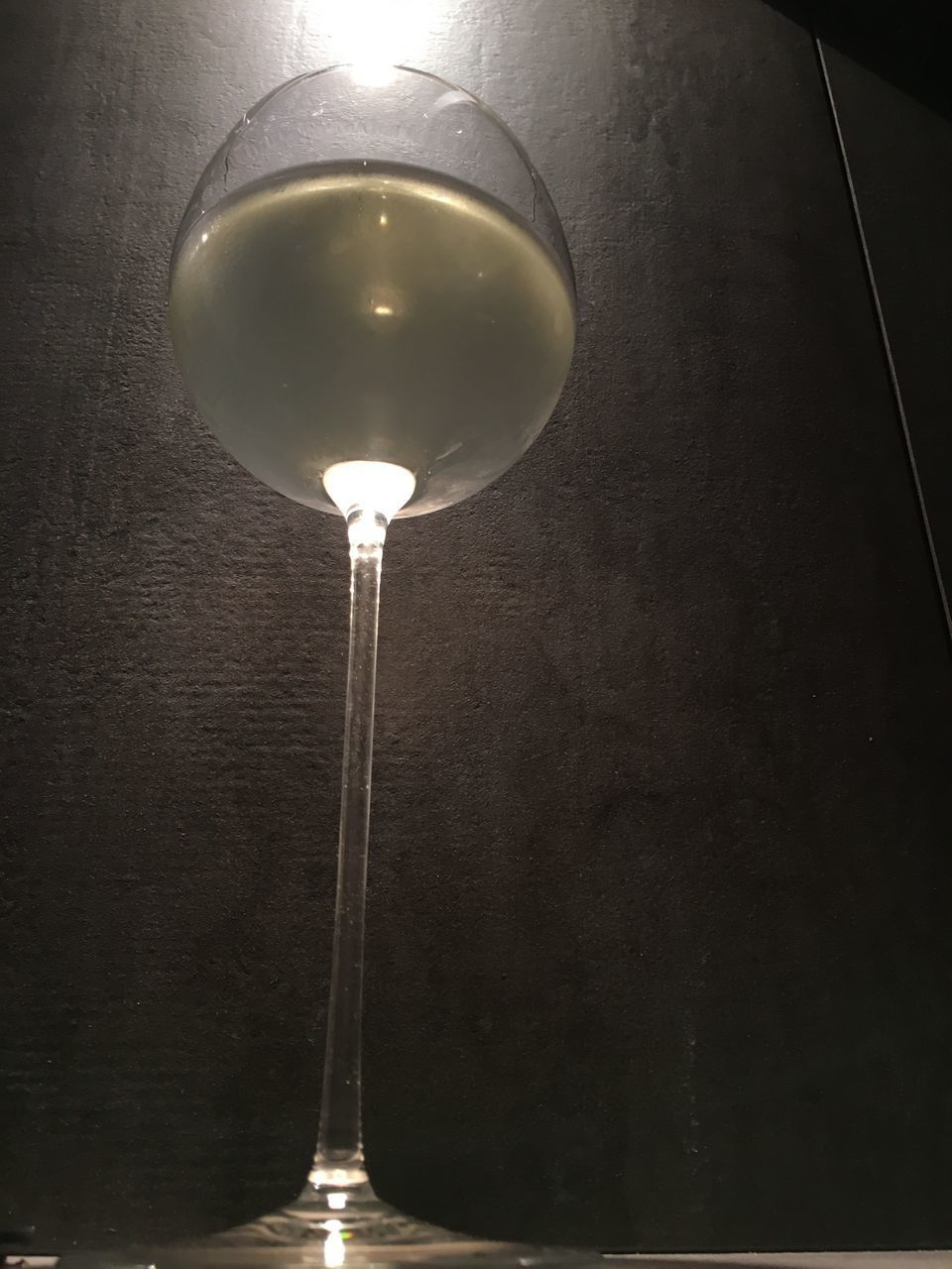 LOW ANGLE VIEW OF WINE GLASS ON ILLUMINATED TABLE