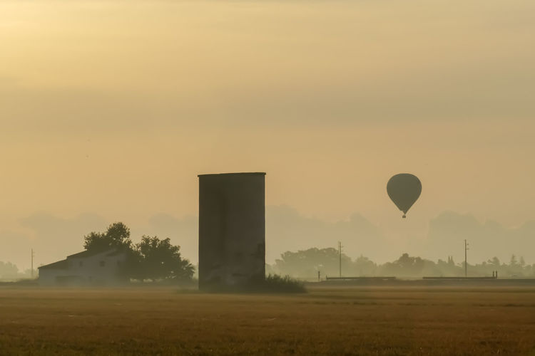 Hot air balloon flying over field during sunset