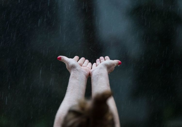 Rear view of woman cupping hands in pouring rain