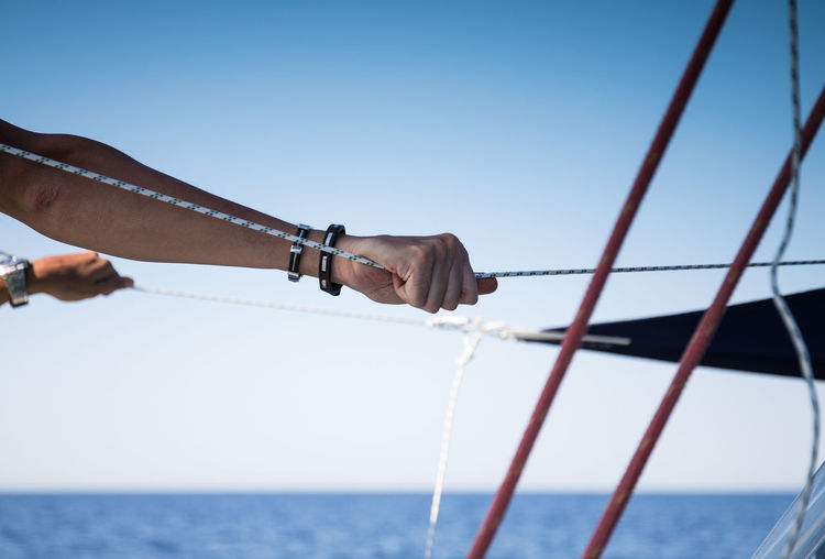 Cropped hand of man holding rope in sailboat against sky