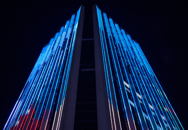 Low angle view of illuminated modern building against sky at night