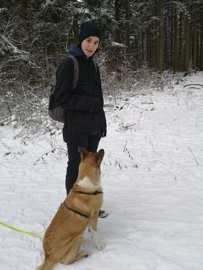 Full length of man with dog on snow