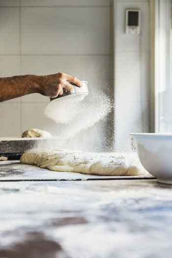Cropped hand sifting flour on dough in kitchen