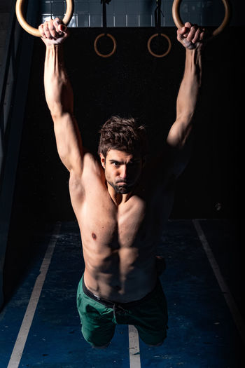 Full length of shirtless man holding camera