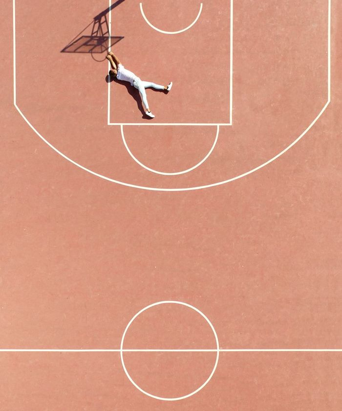 High angle view of man lying on court by basketball hoop shadow
