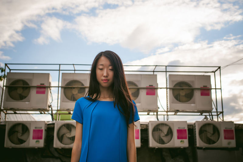 Young woman with eyes closed standing against exhaust fans