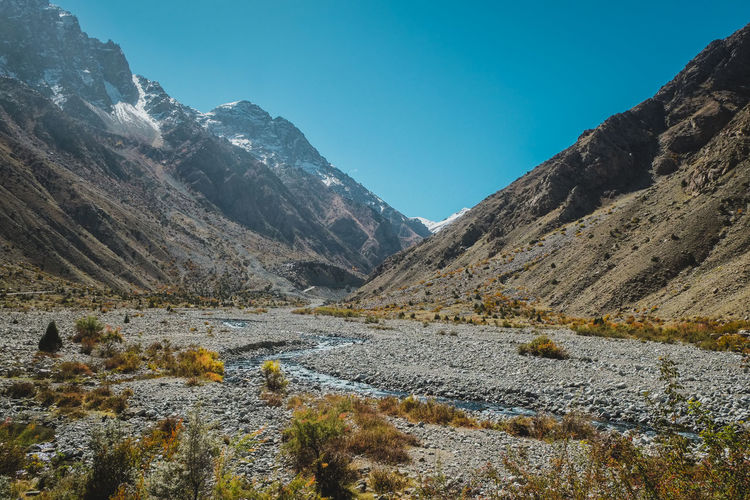 Nature landscape view of wilderness area with mountains in Karakoram range, Skardu. Gilgit Baltistan, Pakistan. Mountain Range Karakoram Skardu Pakistan Snow Capped Mountains Mountain Peak Mountainscape Gilgit Baltistan Green Beautiful Scenery Nature Background Nature Photography Wilderness Area Adventure Travel Eco Tourism Stream Flowing Water Valley Countryside Rural Scene Trekking Hiking Freshness Pure Air Clean Air Panoramic View Panorama Mountaineering Vacations Trees Plants Peaceful Natural Beauty Refreshing Outdoors Environment Ecology Climate Alpine Serenity Tranquility Clear Sky Blue Sky Eco Friendly Organic Nature Exploration Summer Autumn Beauty In Nature Scenics - Nature Tranquil Scene Non-urban Scene Day No People Idyllic Remote Land