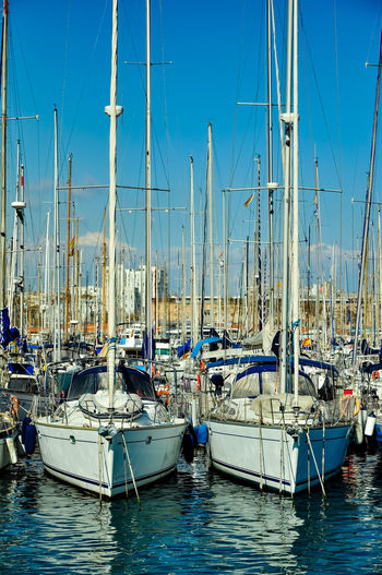 Sailboats moored on harbor against clear blue sky
