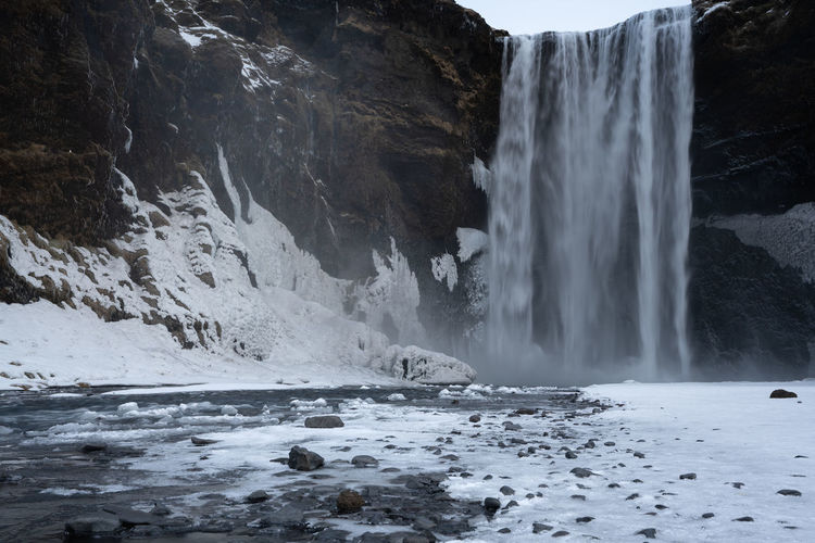 Skogafoss, Iceland No People Nature Beauty In Nature Water Scenics - Nature Outdoors Power In Nature Flowing Water Skogafoss Travel Tourism Tourist Attraction  Waterfall Nature Landscape River Winter Wintertime Snow Rock - Object Mountain Cold Temperature Countryside