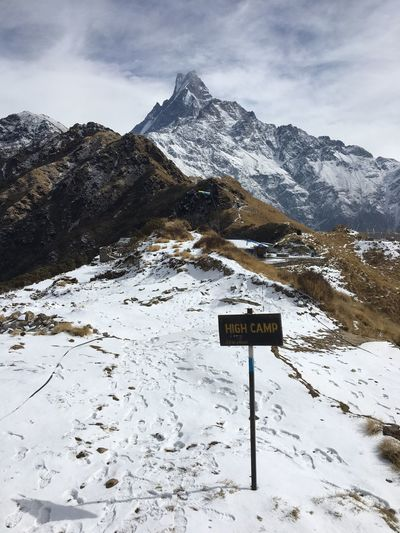 Road sign on snow covered mountain against sky