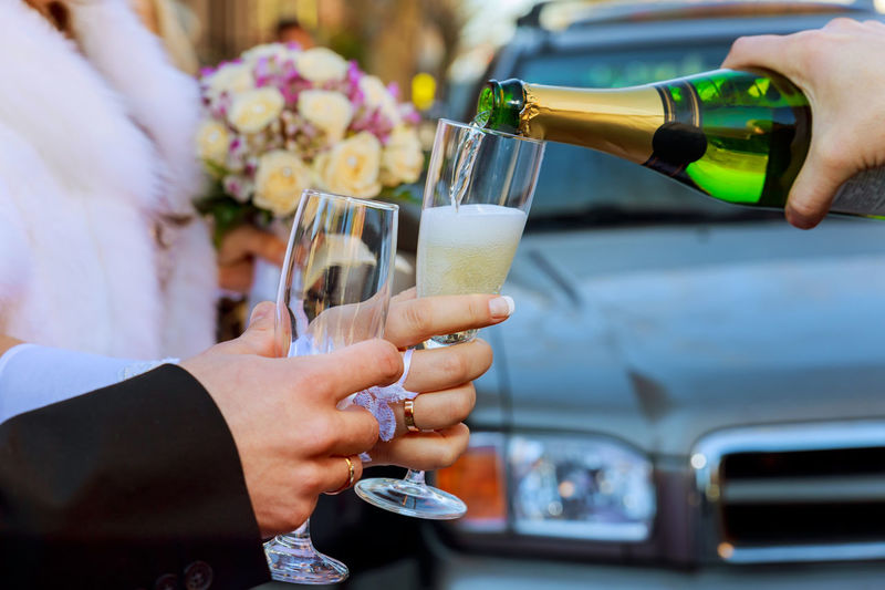 Cropped Hand Pouring Champagne In Glass Held By Bride