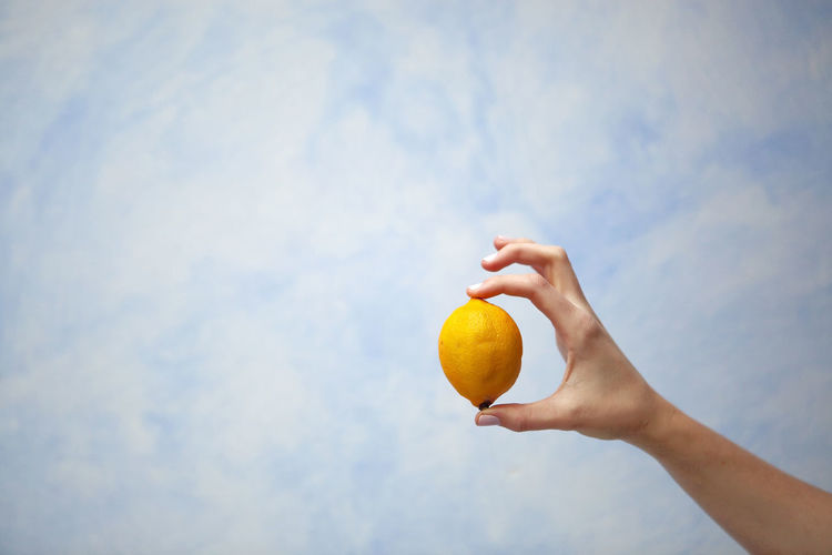 Low Angle View Of Hand Holding Fruit Against Sky