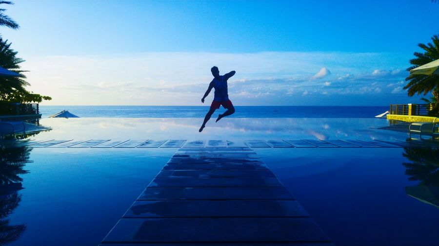 Man Jumping Over Pier Against Blue Sea During Sunset