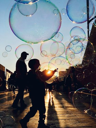 JOY. Kid Playing Kid Sky Bubble Men Real People Nature Group Of People #urbanana: The Urban Playground City Lifestyles People Street Silhouette Outdoors Summer In The City Moments Of Happiness