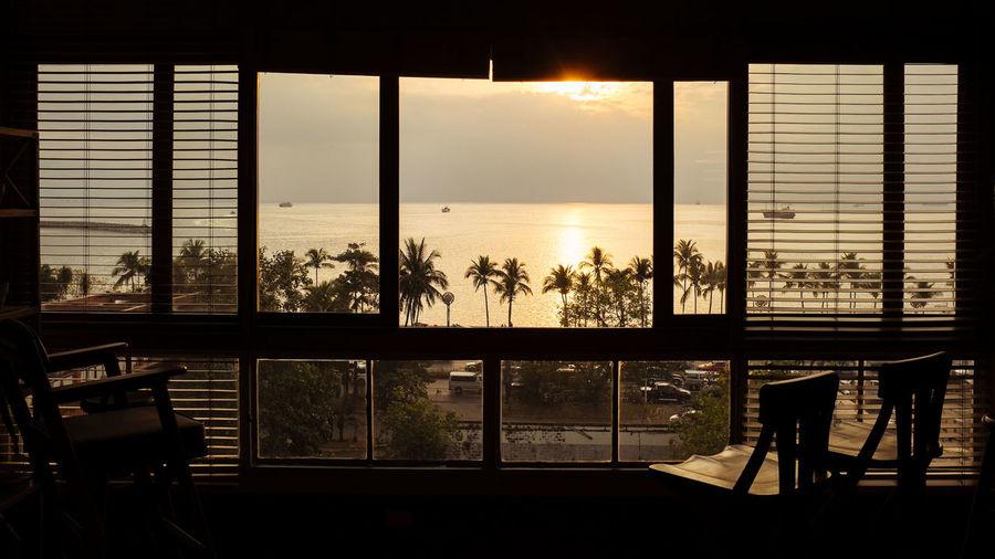 Sea seen through window at sunset