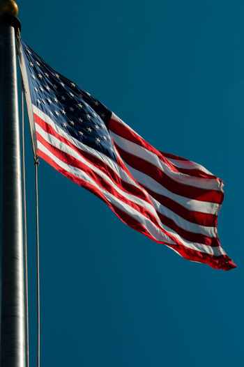 Abstract American Flag Blue Clear Sky Cultur Flag Flag Pole Guidance Identity Low Angle View National Flag Negative Space Outdoors Patriotism Pole Safety Street Light Striped Symbol Technology Wind