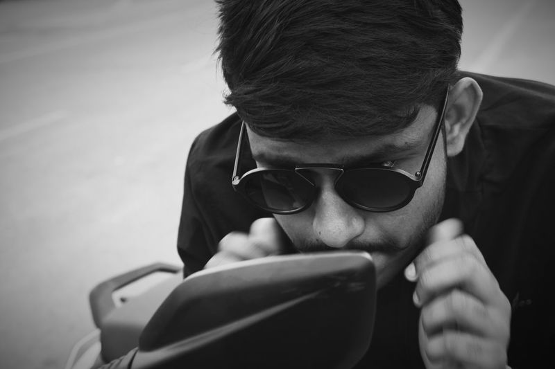 Young Man Looking Into Side-View Mirror Of Motorcycle