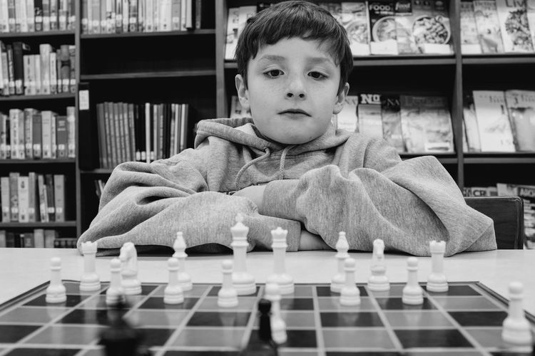Cute boy playing chess in library