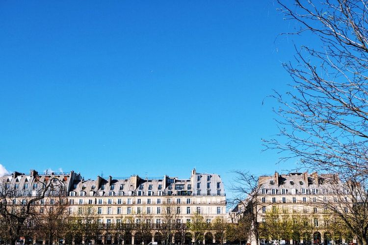 Low Angle View Of Buildings Against Clear Blue Sky On Sunny Day