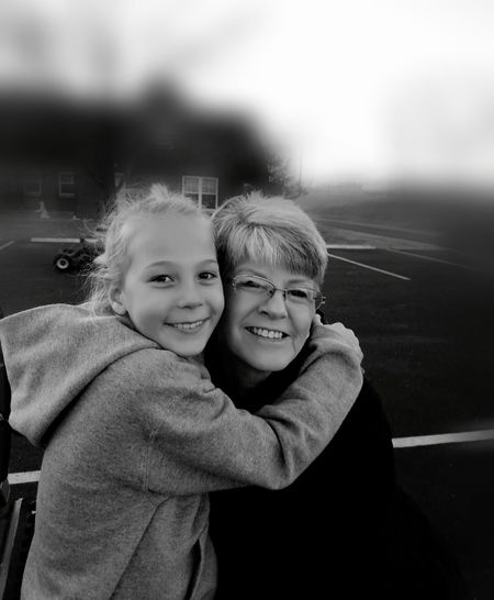 Portrait of smiling grandmother and granddaughter embracing at playground