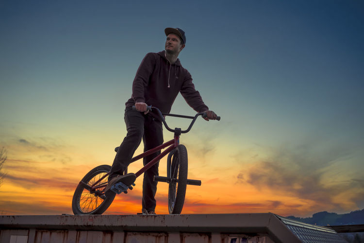 Low angle view of man on bicycle against sky during sunset