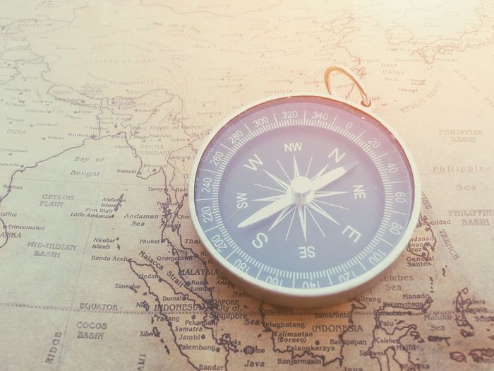 Compass on paper map Direction Guidance Business Compass Navigation Navigator  Travel Trip Map Way Journey Advanture Voyage Lifestyle Lost Cartography Geography Success Arrow Destination Tourist North South East West